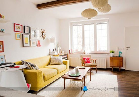 چیدمان اتاق نشیمن با یک کاناپه راحتی زرد رنگ و یک صندلی چوبی / عکس