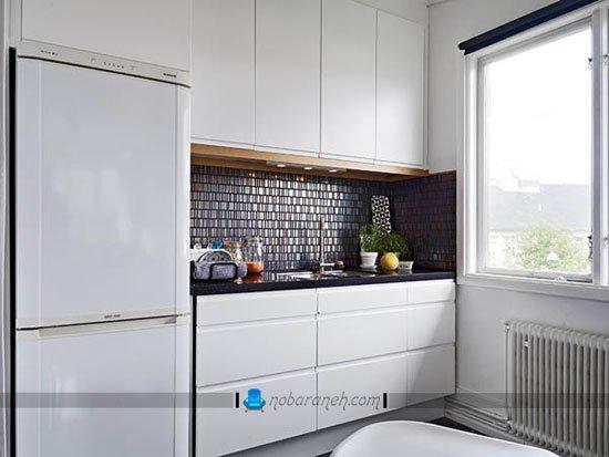 آشپزخانه کوچک با کابینت های سفید و کاشی سیاه رنگ / عکس
