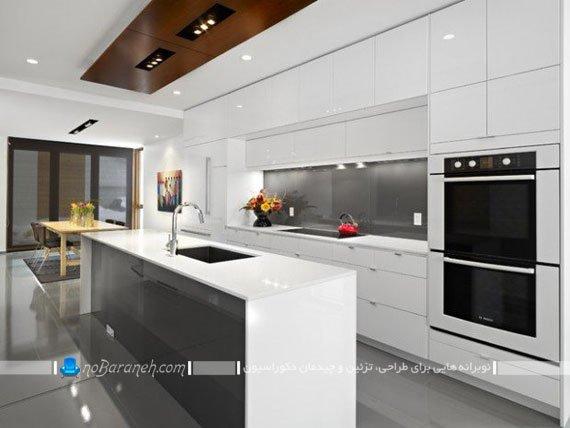 آشپزخانه مدرن با میز جزیره ای بزرگ. مدل های نصب سینک ظرفشویی روی میز جزیره و اپن آشپزخانه. دکوراسیون و چیدمان آشپزخانه جزیره با کابینت گلاس سفید رنگ.