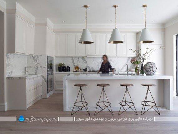 اپن جزیره ای سفید رنگ با صفحه سنگی. مدل های جدید جزیره برای آشپزخانه های بزرگ. نورپردازی میز جزیره با چراغ سقفی فانتزی